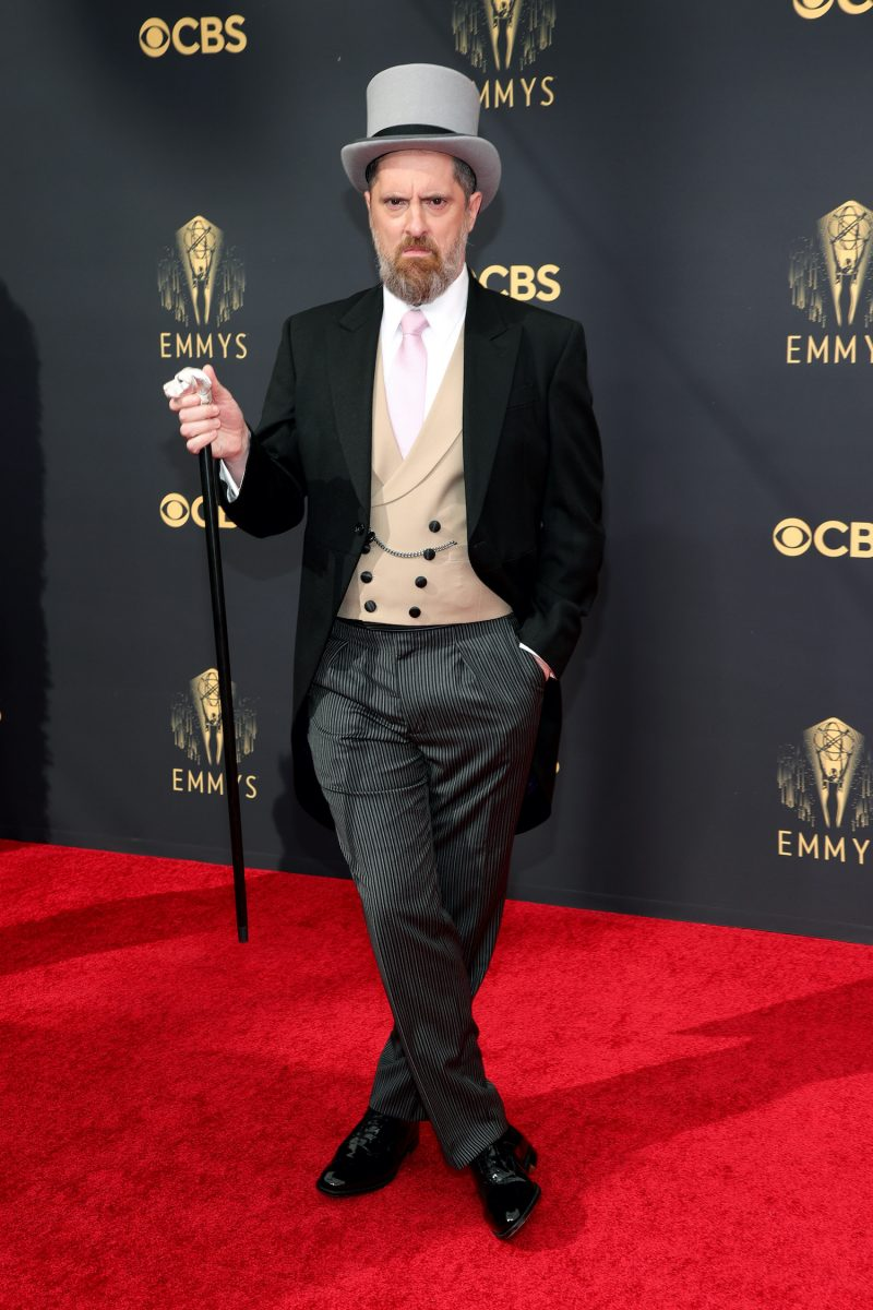 Brendan Hunt wears a tuxedo with tails, top hat, and cane on the red carpet at the 2021 Emmys