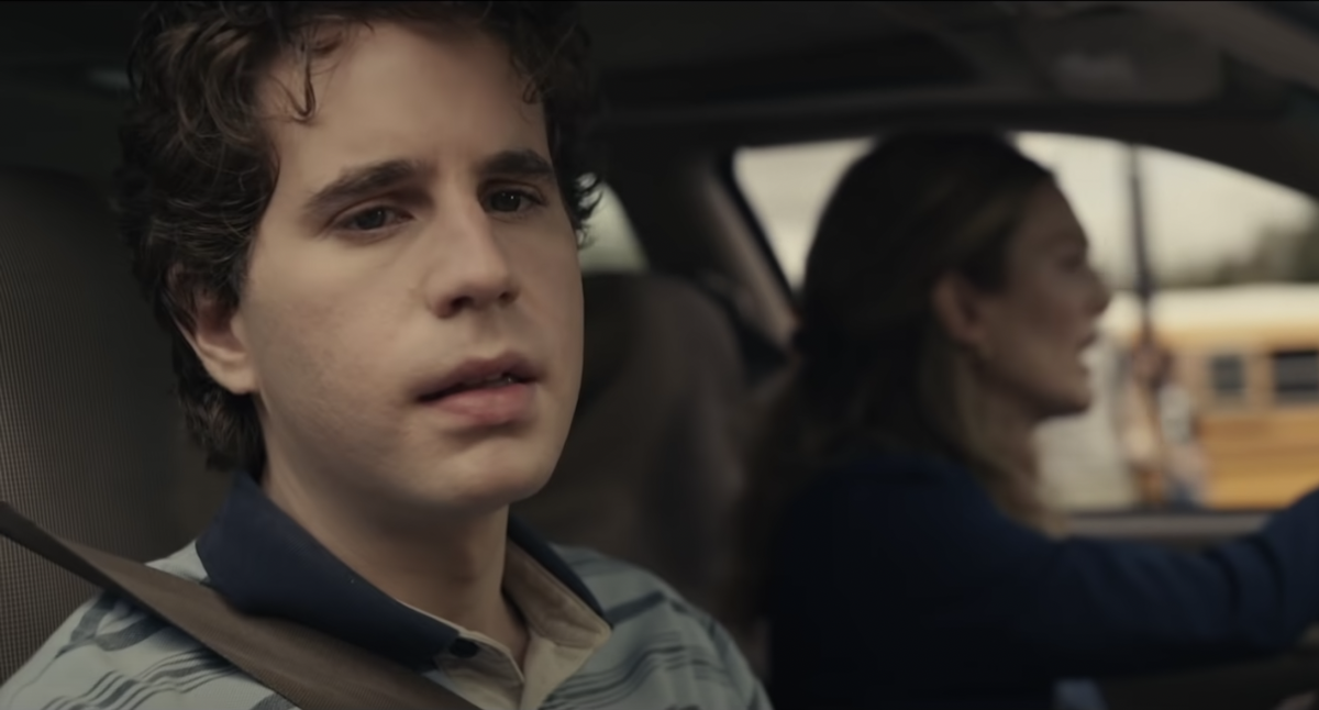 Ben Platt is seen in the 'Dear Evan Hansen' movie trailer. He sits in a car looking out the window with a concerned look on his face and wearing the character's signature blue striped polo shirt. Julianne Moore is in the driver's seat playing his mother, Heidi.