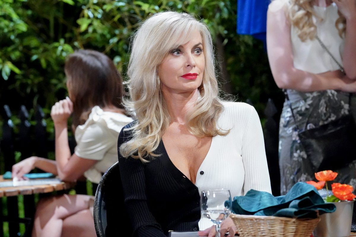 Eileen Davidson sitting down in a black and white outfit and red lipstick
