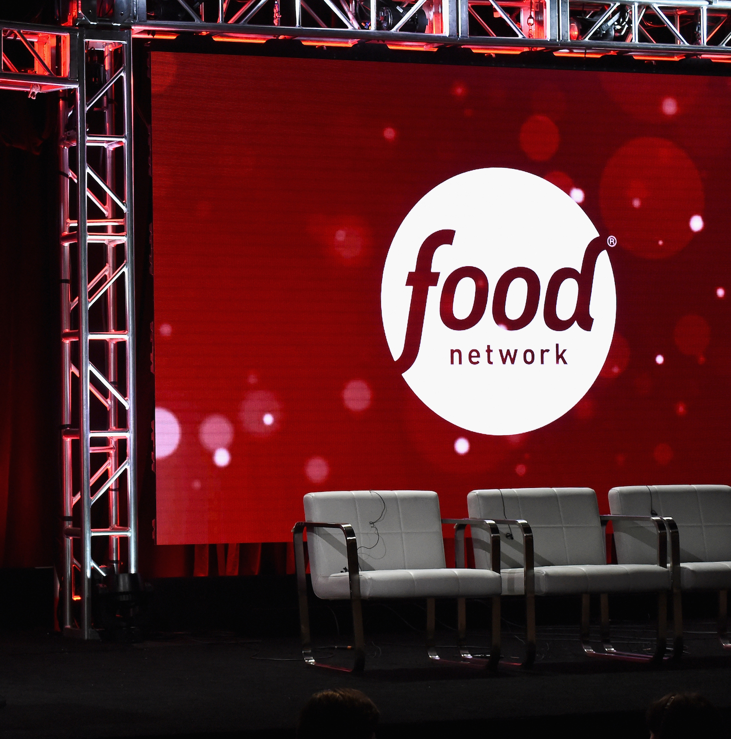 Food Network logo projected on a screen with three gray chairs in front