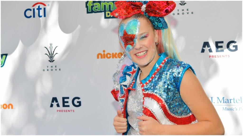 JoJo Siwa poses in a glittery outfit on the red carpet.