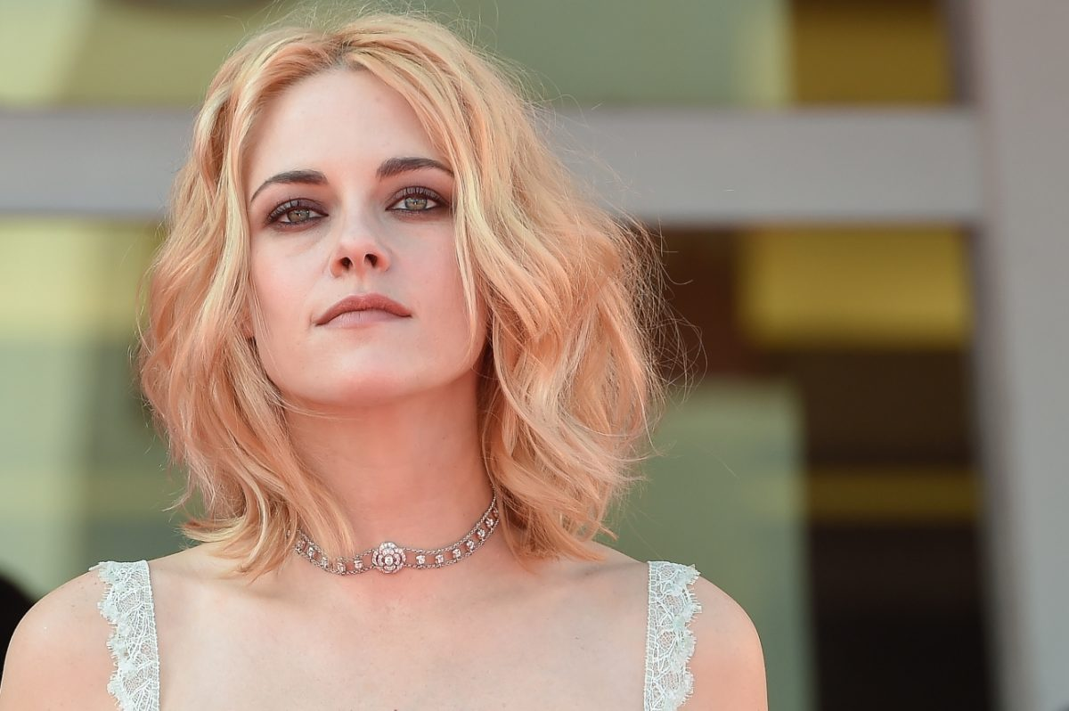 Kristen Stewart looks on while posing on the red carpet at the premiere of 'Spencer'