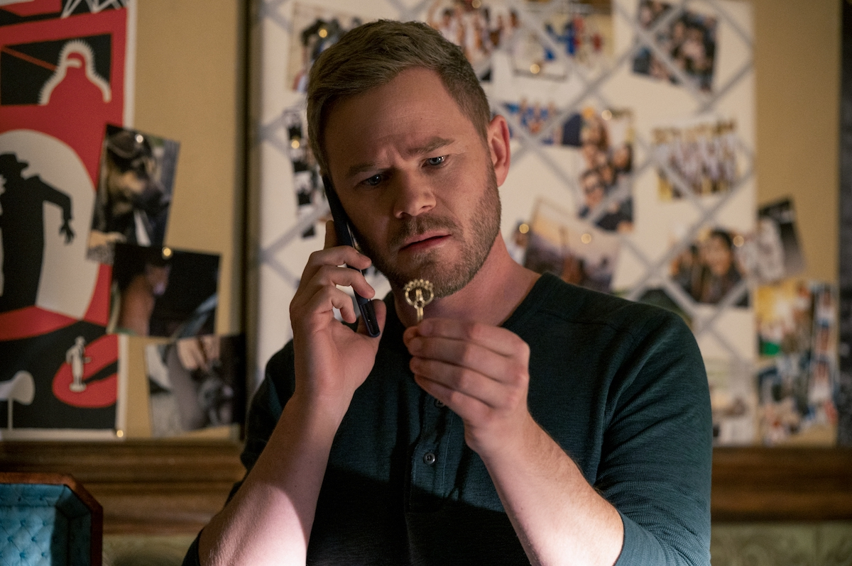 Aaron Ashmore as Duncan Locke staring at a key in a production still from 'Locke & Key' Season 2