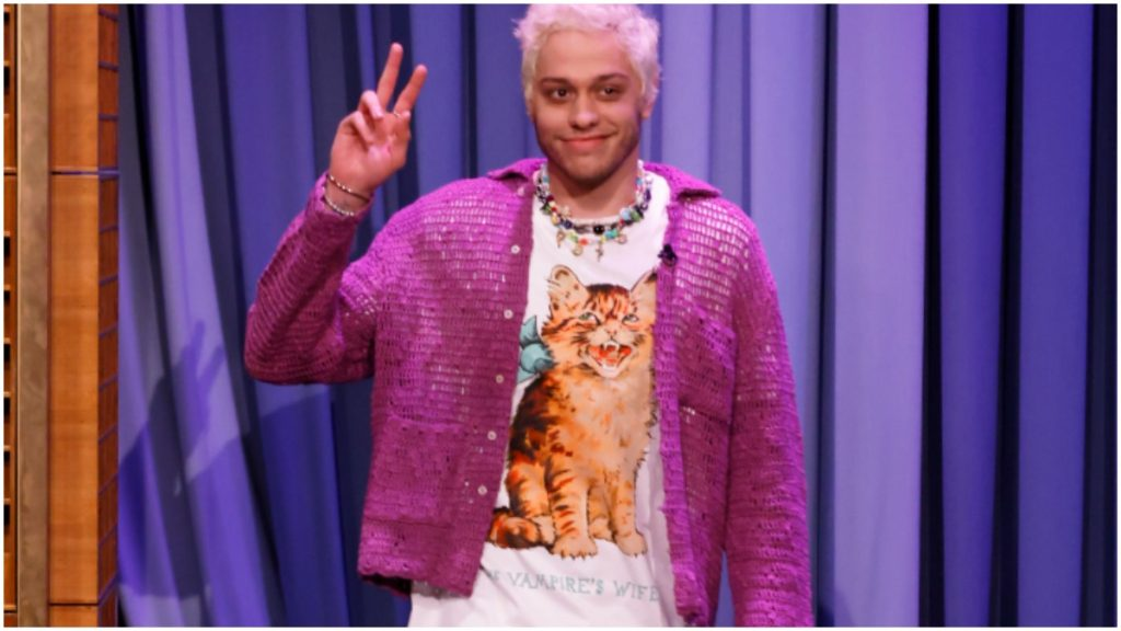Pete Davidson wears a lavender jacket and a graphic t-shirt.