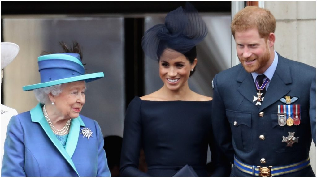 Queen Elizabeth, Meghan Markle, Prince Harry pose at a royal event.