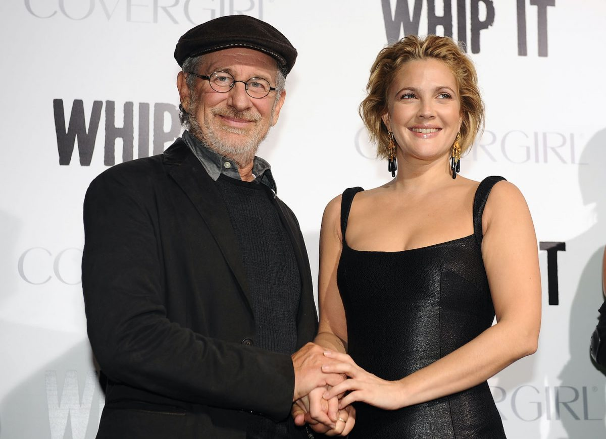 Steven Spielberg and Drew Barrymore both wear black and smile while holding hands on the red carpet at the premiere of 'Whip It' in 2009
