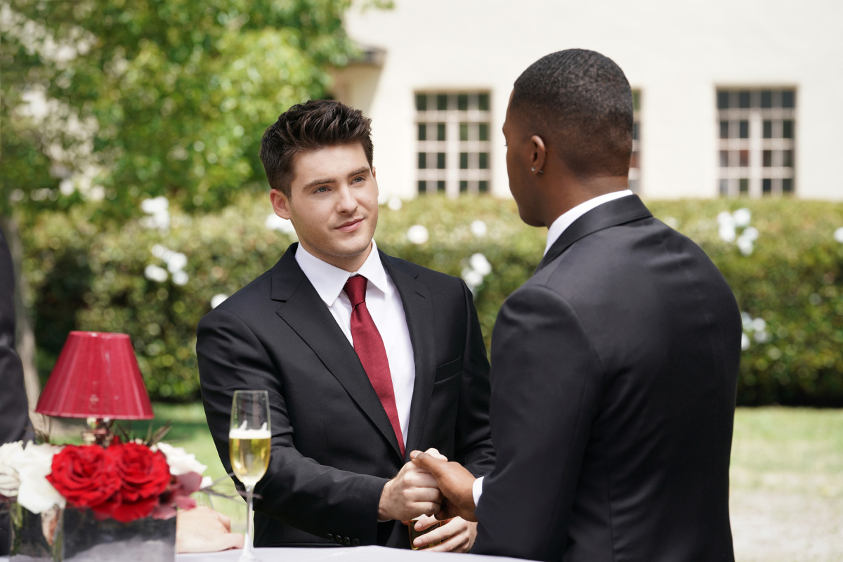'All American' Season 4 actors Cody Christian and Daniel Ezra, as their characters, shake hands. Both of them are wearing black suits over white shirts and a red tie.
