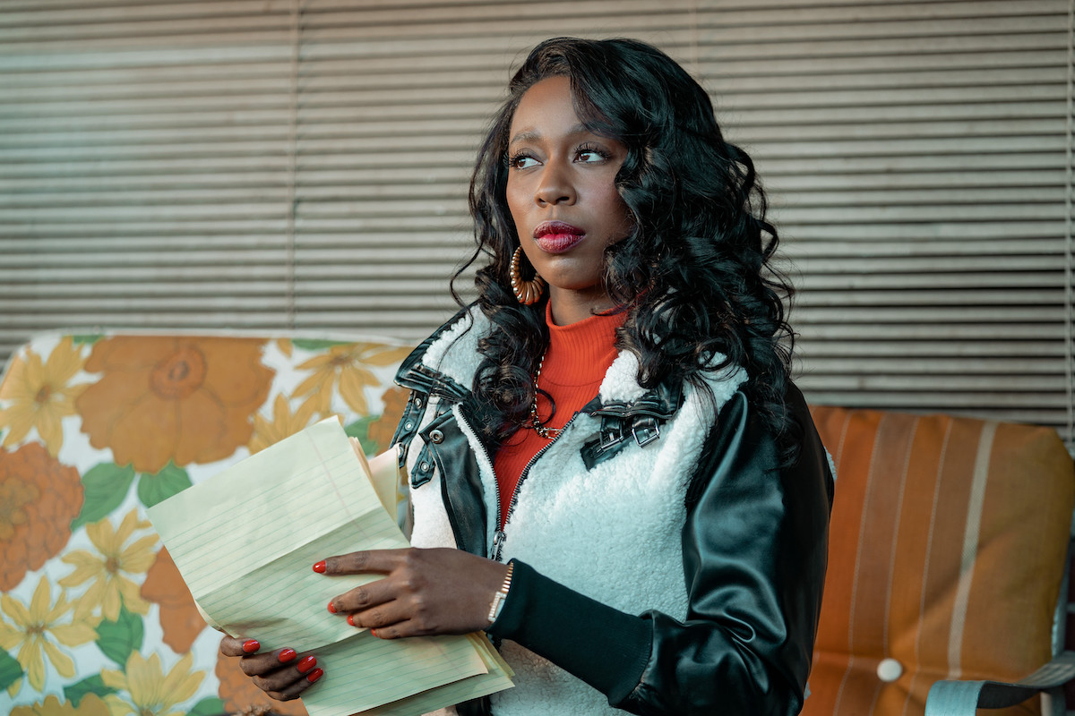Kash Doll as Monique holding loose sheets of paper in 'BMF'