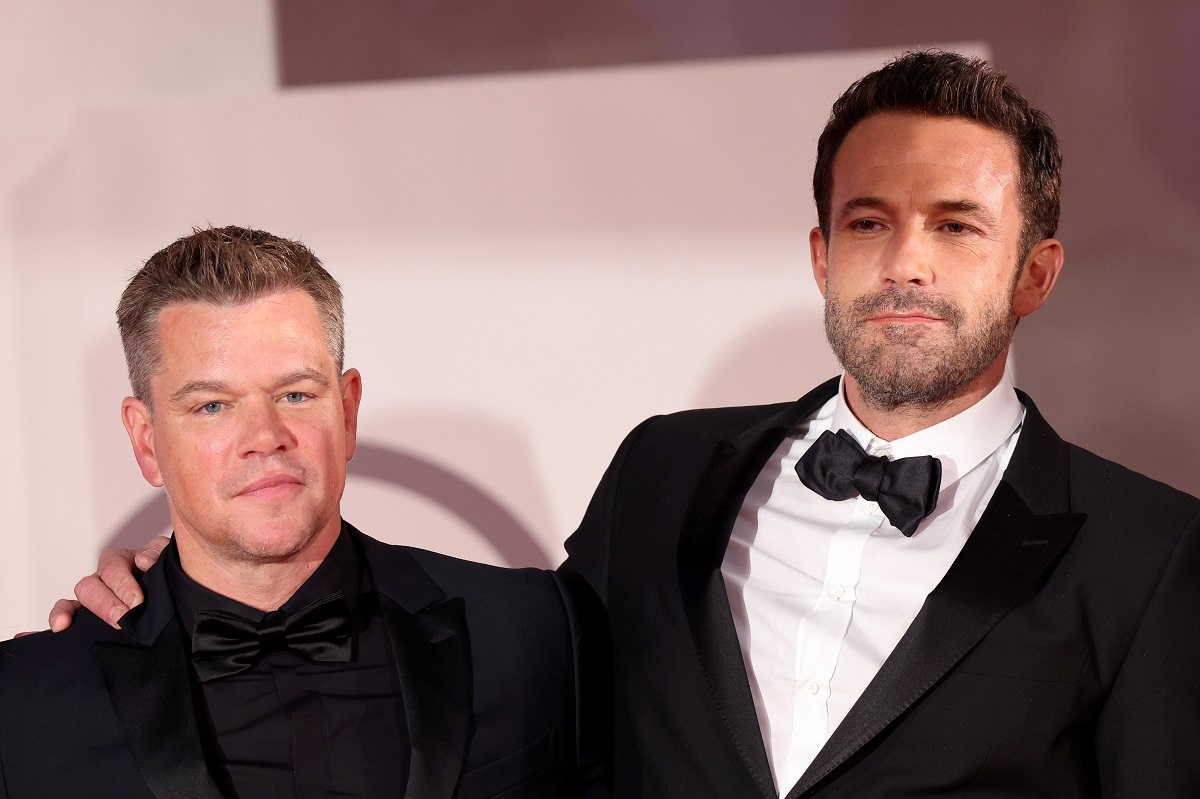 Matt Damon and Ben Affleck smiling at each other while wearing suits