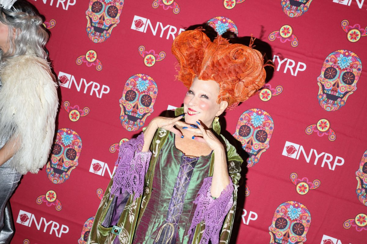 Bette Midler dressed as Winifred Sanderson from 'Hocus Pocus.' She's returning for 'Hocus Pocus 2' on Disney+. In the photo, she's wearing the witch's orange wig and green and purple dress.