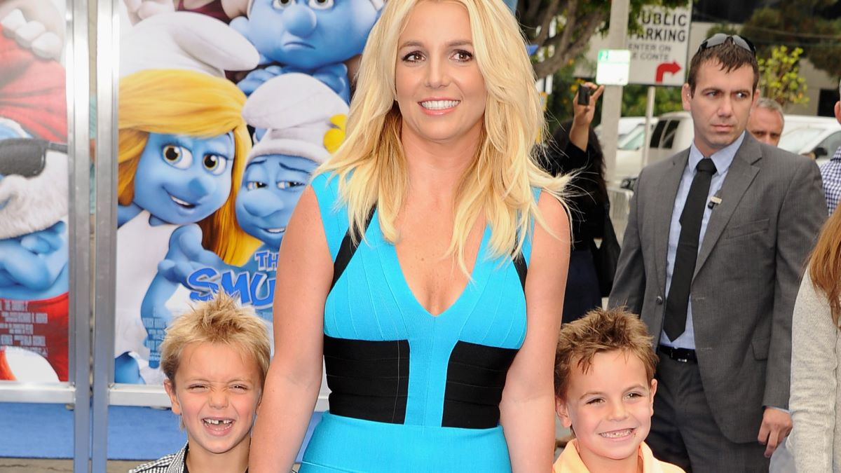 Britney Spears smiles in a blue dress in between her young sons