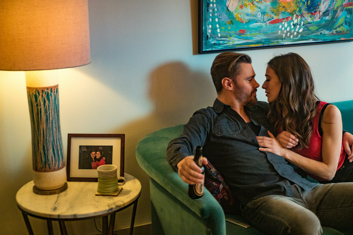 Kim and Adam on a couch, cuddling, smiling in a scene from 'Chicago P.D.'