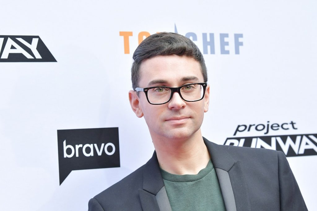 'Project Runway' Season 4 winner Christian Siriano in a black suit, green shirt, and black rimmed glasses posing for photographers on the red carpet.