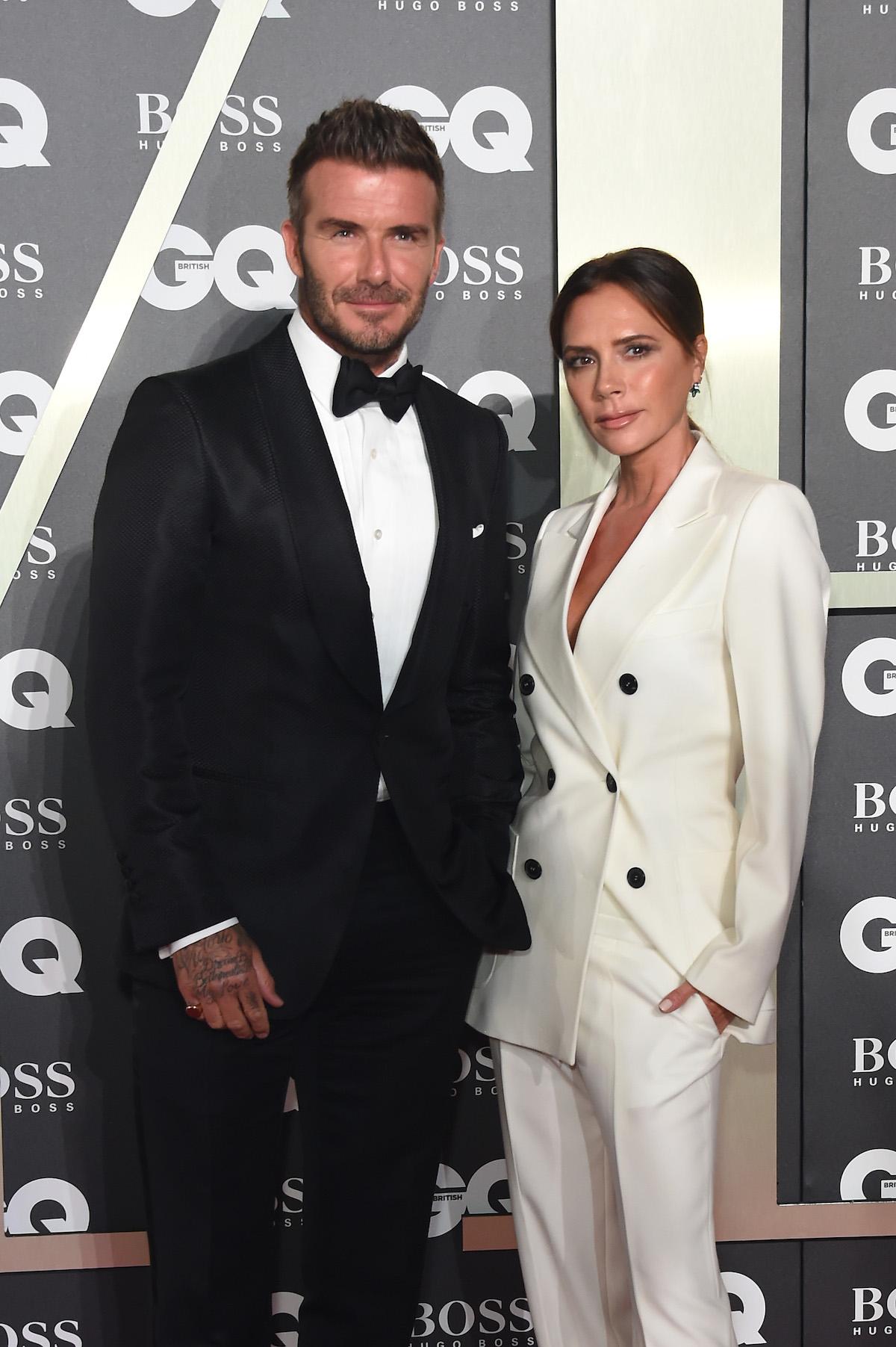 David Beckham and Victoria Beckham pose together at an event.