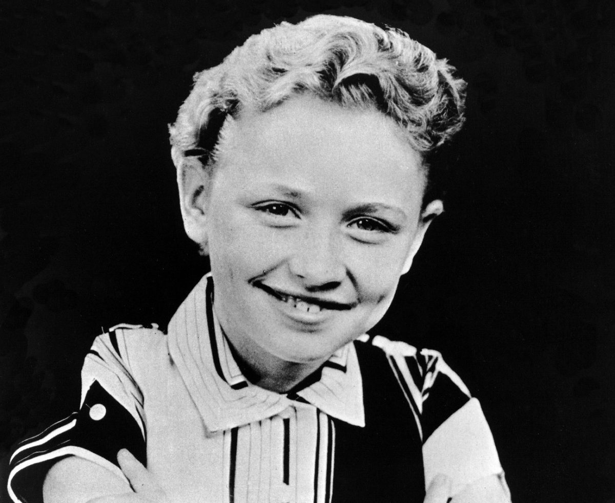 A black and white photo of Dolly Parton as a child sitting in front of a black background.