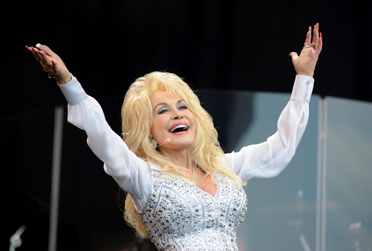 Dolly Parton wears a white outfit and performs onstage. Dolly Parton's husband Carl Dean Thomas rarely basks in the spotlight like her.