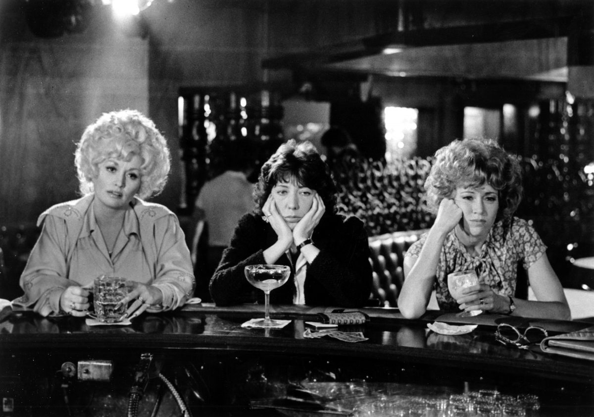 Dolly Parton, Lily Tomlin, and Jane Fonda sitting at a bar in the movie '9 to 5.'