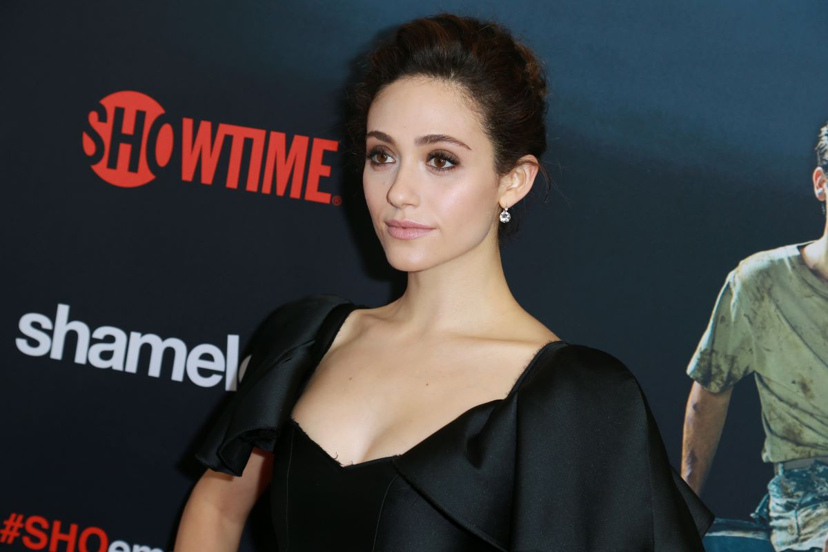 Emmy Rossum in black, looking away from camera