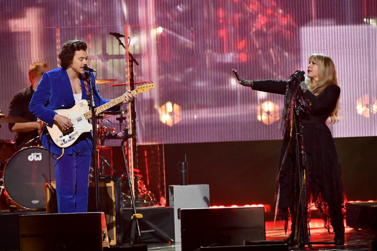 Harry Styles and Stevie Nicks perform together on stage at the Rock and Roll Hall of Fame. Styles plays guitar.