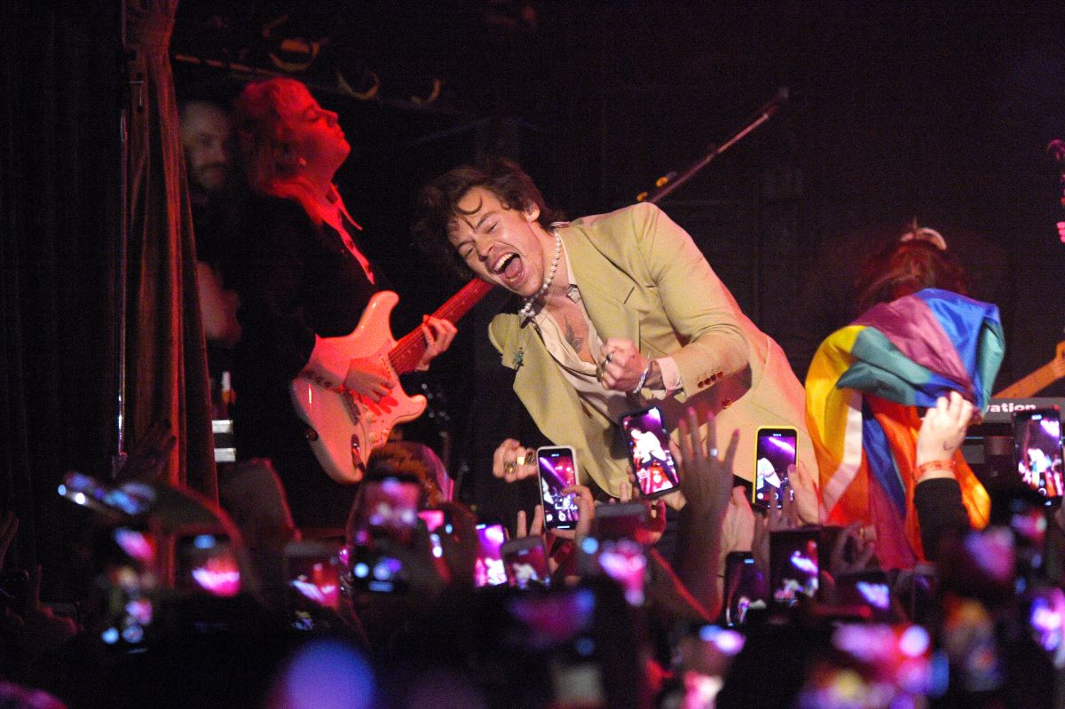 Harry Styles performs in a tan suit, on stage in front of a crowd