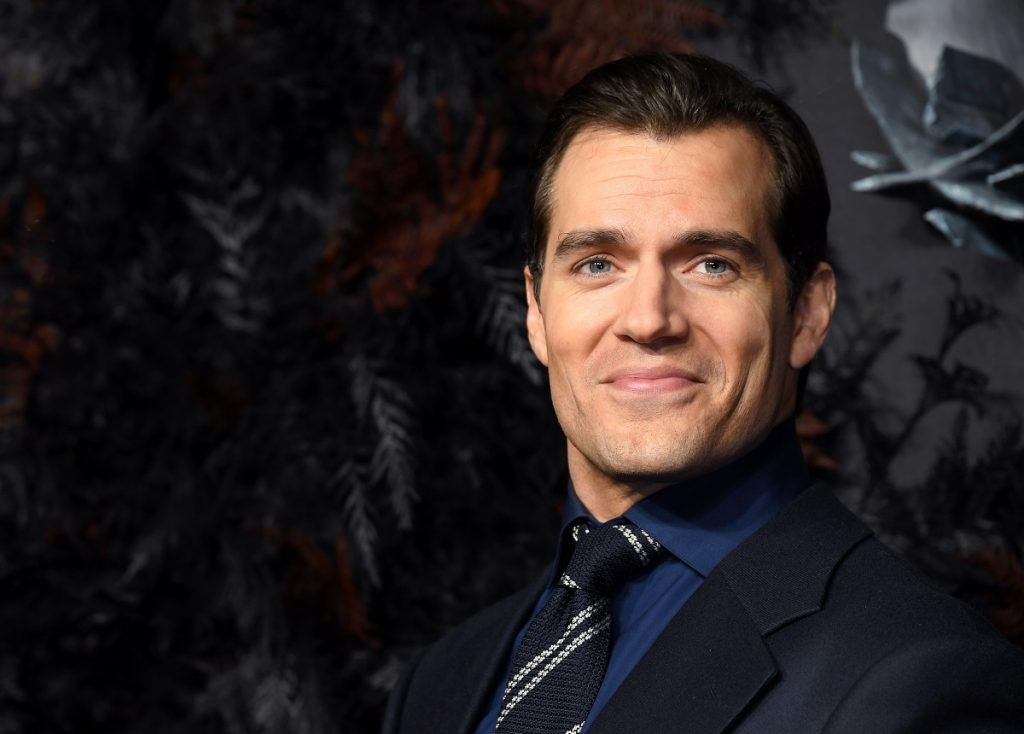 Henry Cavill smiling in a suit