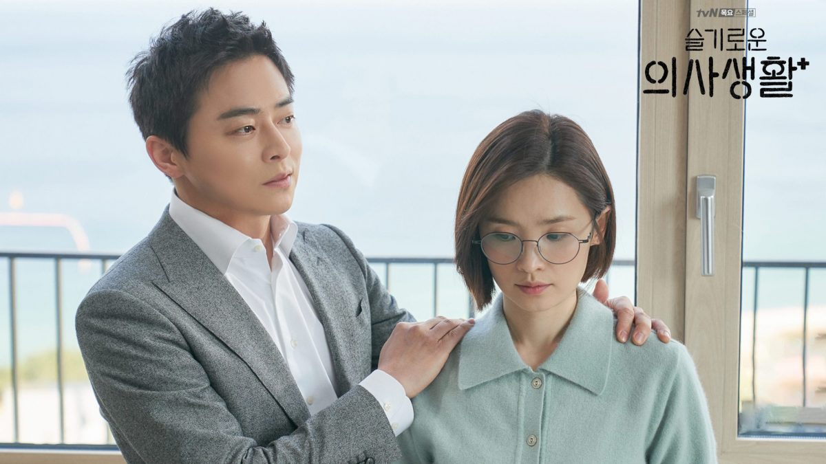 Ik-Jun and Song-Hwa in 'Hospital Playlist' K-drama with Ik-Jun holding onto Song-hwa's shoulders
