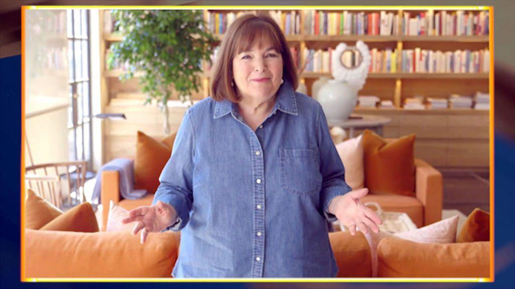 Ina Garten stands in front of an orange couch while wearing a blue short and holding her hands out.