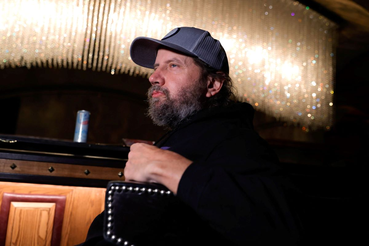 Jamie Kennedy from the side with a beard and cap.