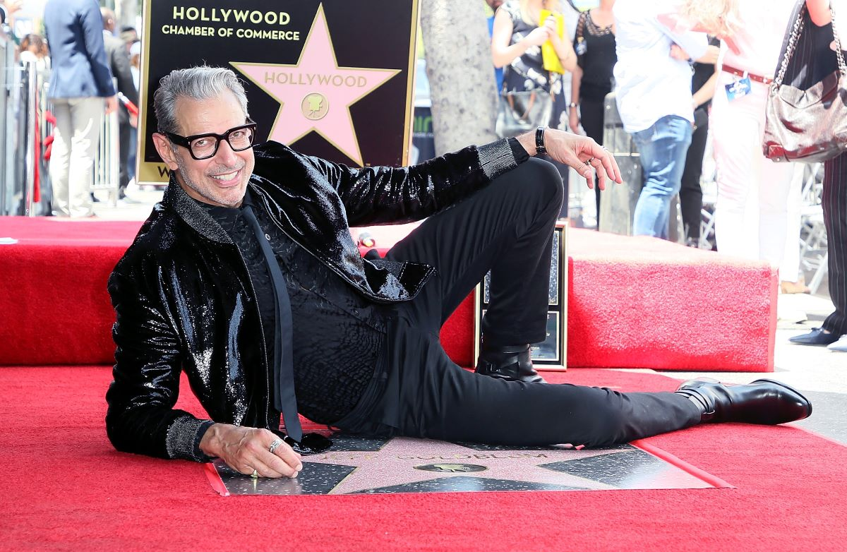 Jeff Goldblum wearing glasses and dressed in black, reclined with hand rested on knee