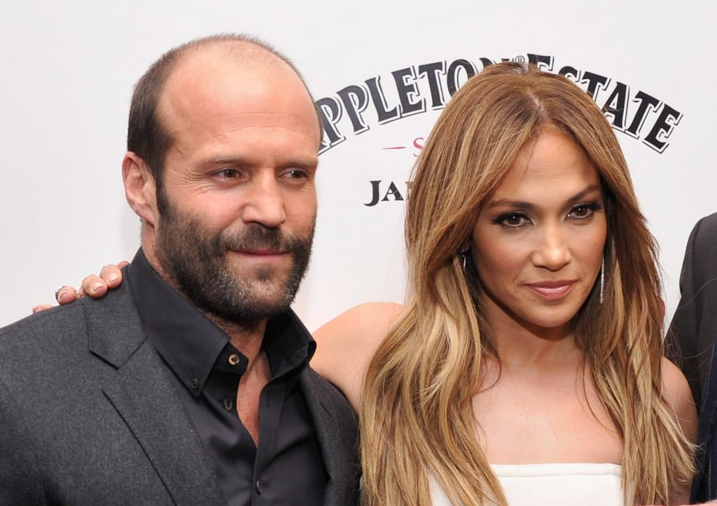 Jennifer Lopez appears in a white dress and stands next to Jason Statham at a movie premiere for 'Parker.'