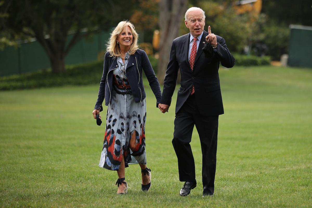 Jill Biden and Joe Biden hold hands and walk across a grassy lawn together.