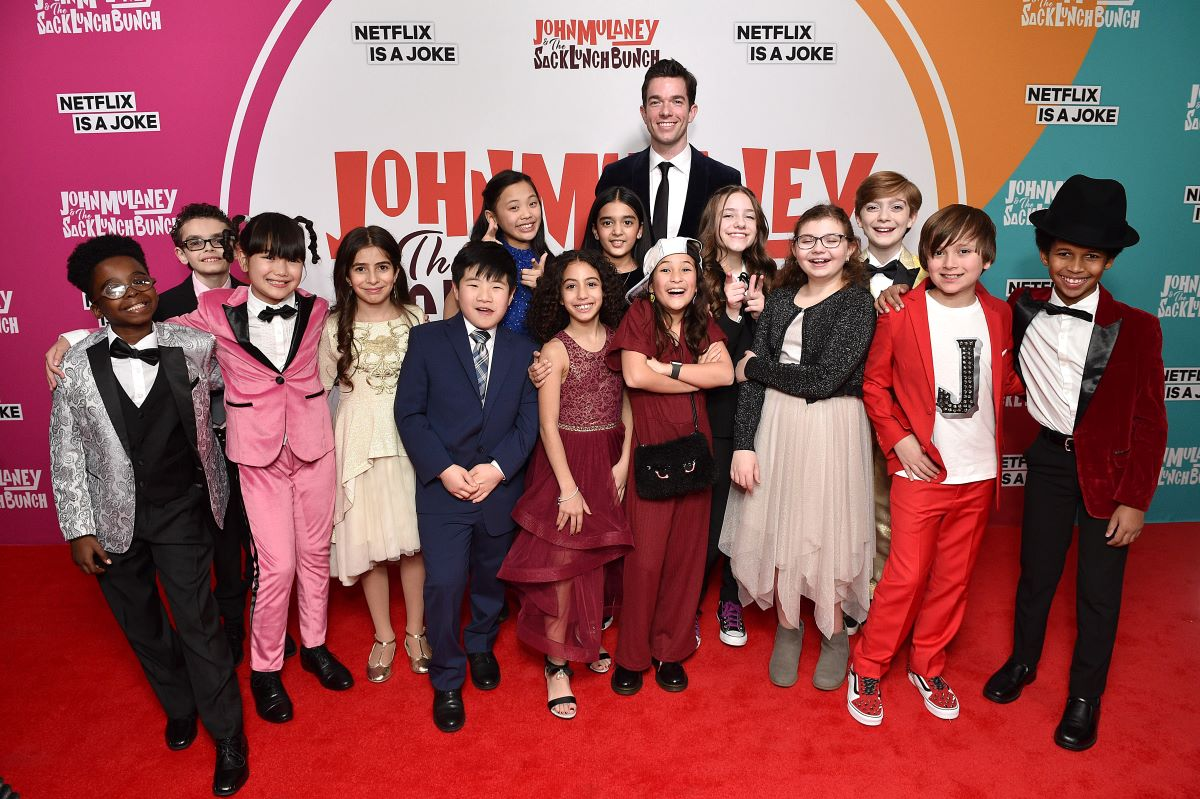 John Mulaney in a black suit and tie surrounded by cast of 'The Sack Lunch Bunch'