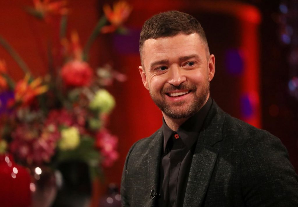 Justin Timberlake, known to an average car, dressed in a black suit with a black shirt in front of a red background with a floral arrangement off to the side.