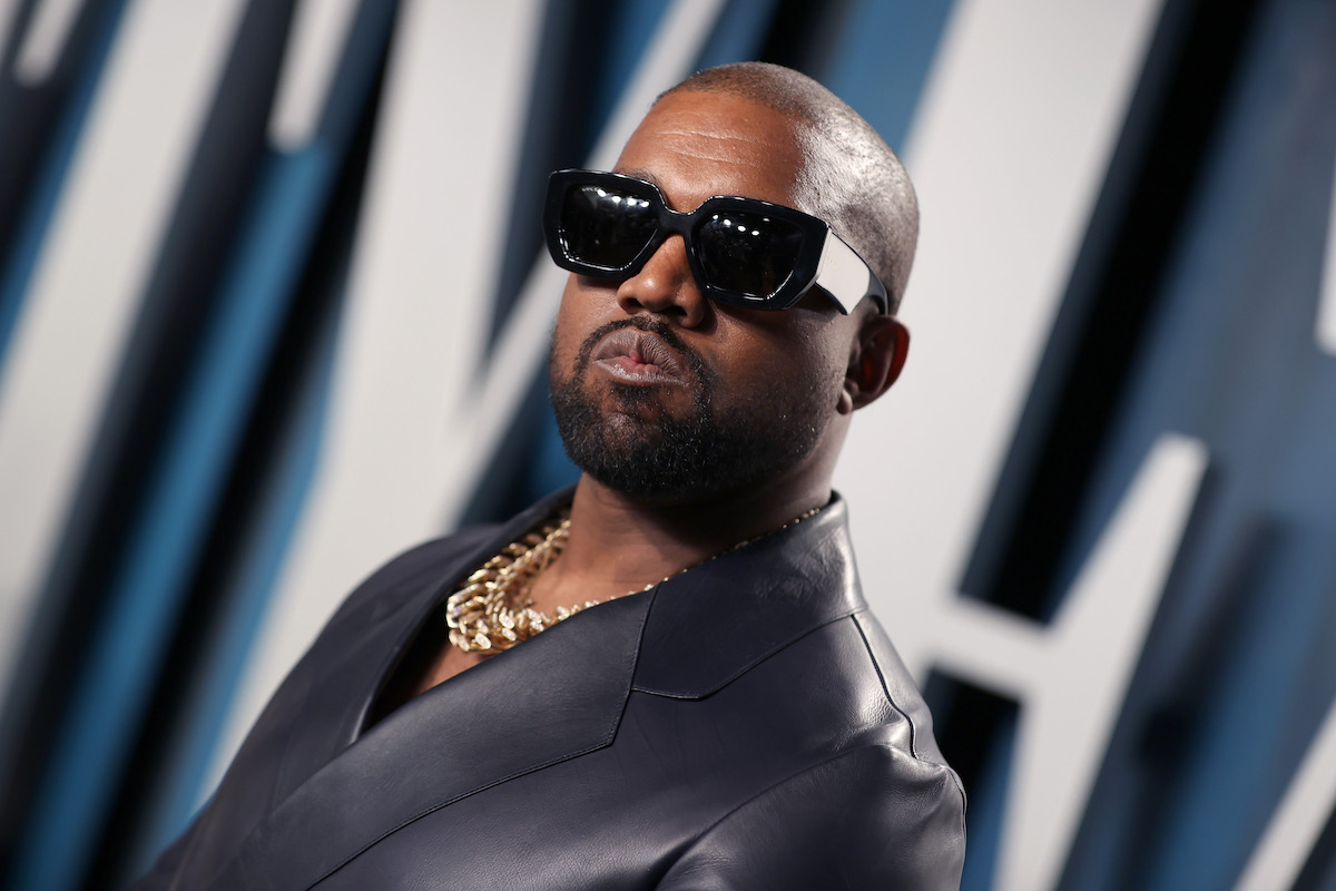 Kanye West poses for photographers while wearing black sunglasses, a gold chain, and black jacket.