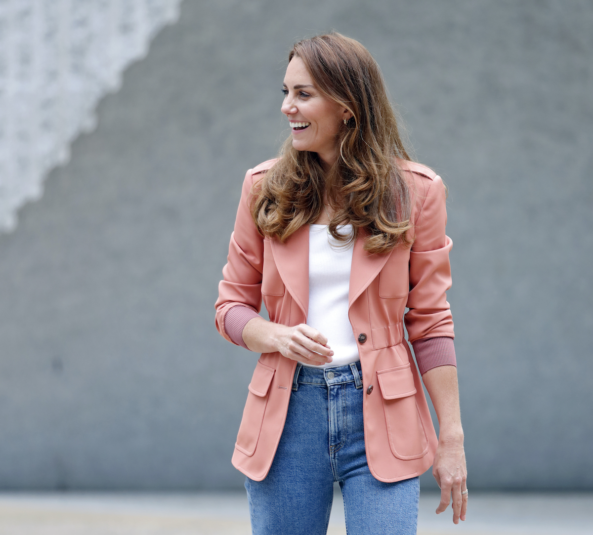 Kate Middleton laughing, turned to the right, wearing a pink blazer, white shirt, and high waisted jeans