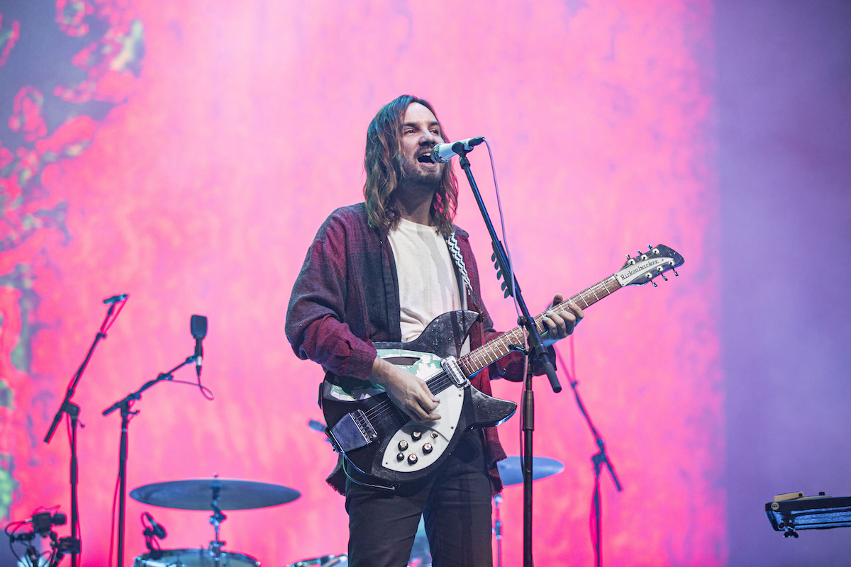 Kevin Parker from the group Tame Impala performs on stage with a guitar.