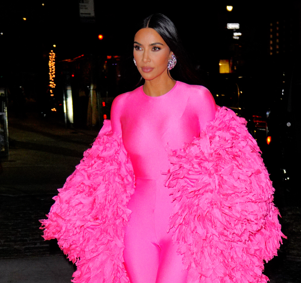 Kim Kardashian West arrives at the afterparty for Saturday Night Live. She is wearing a pink catsuit with large earrings and a pink feather wrap.