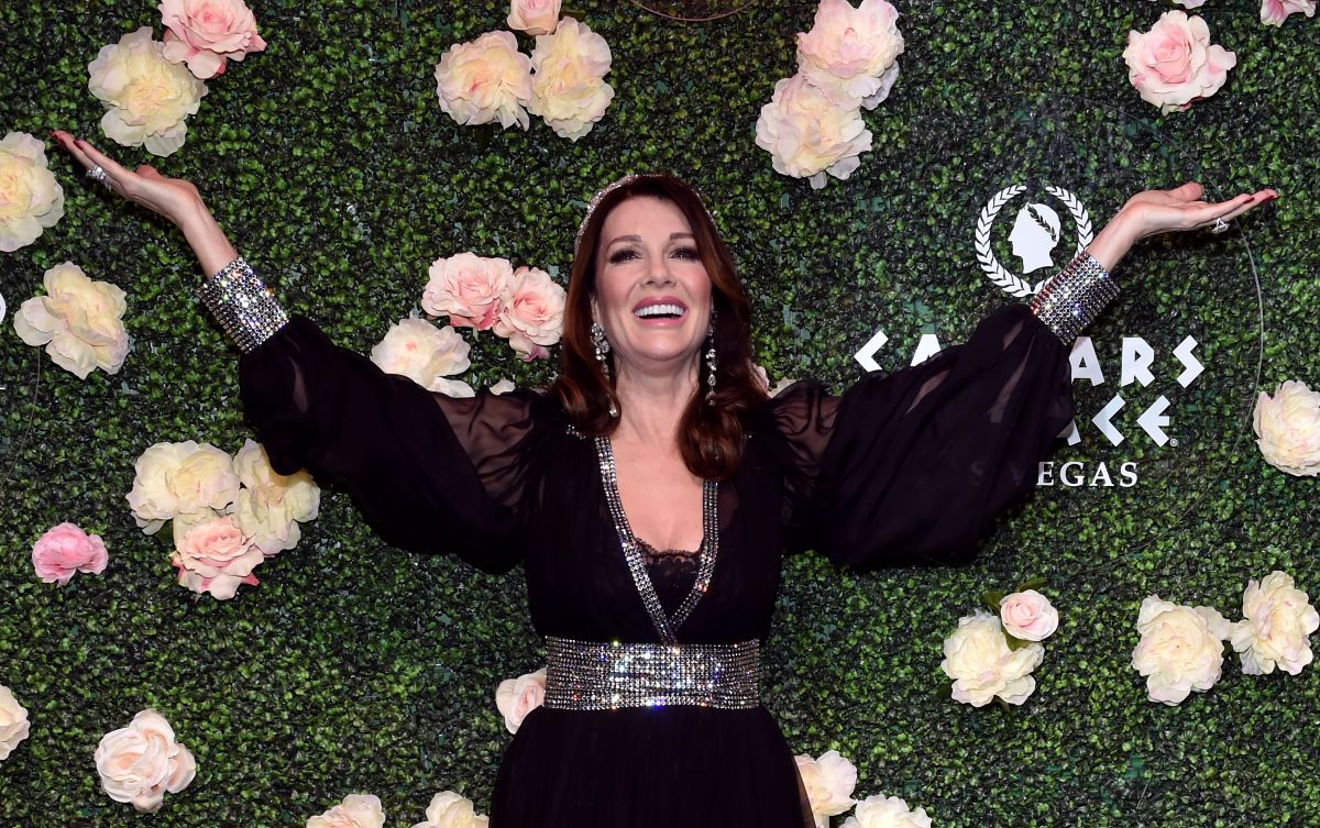 Lisa Vanderpump raises both hands and smiles in black dress with glittery accents