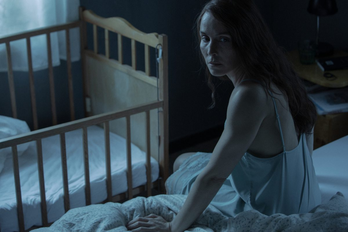 'Lamb' actor Noomi Rapace as Maria sitting on her bed looking concerned