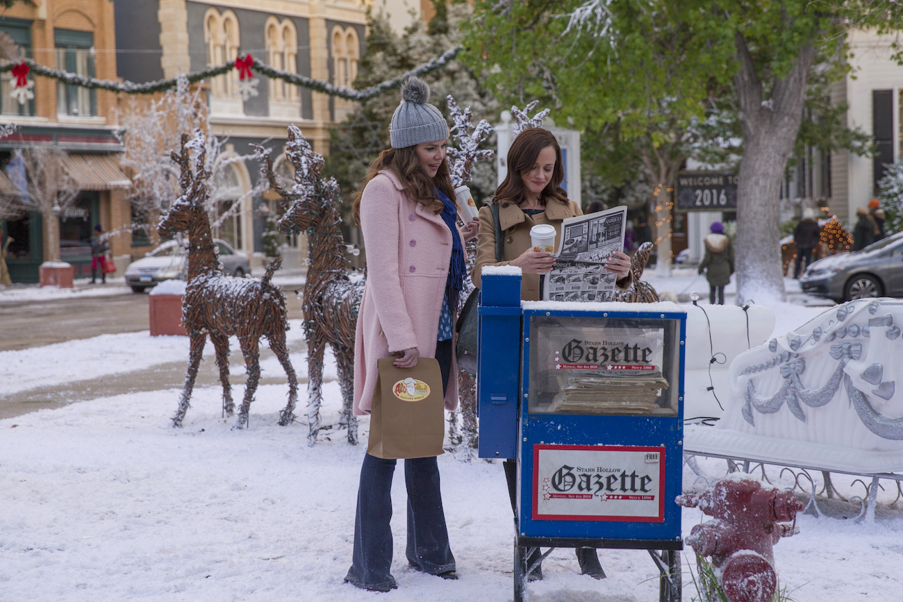 Lauren Graham and Alexis Bledel look at a newspaper while standing next to a mailbox in a scene from 'Gilmore Girls: A Year in the Life'