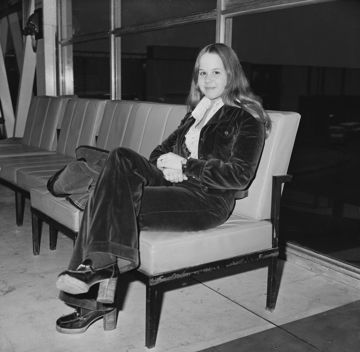 Linda Blair smiling, seated, in a black and white photo from 1974