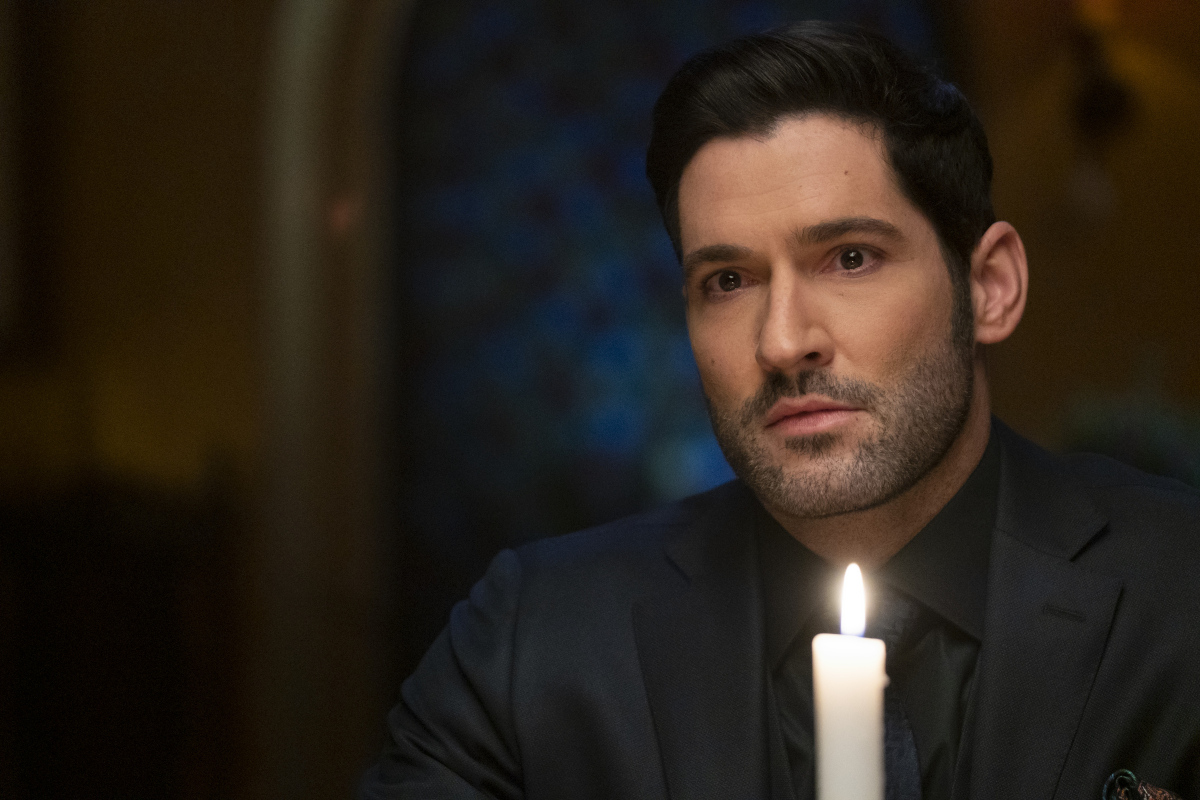 Tom Ellis as Lucifer Morningstar in the spooky series 'Lucifer.' Lucifer is sitting behind a lit candle wearing an all-black suit.