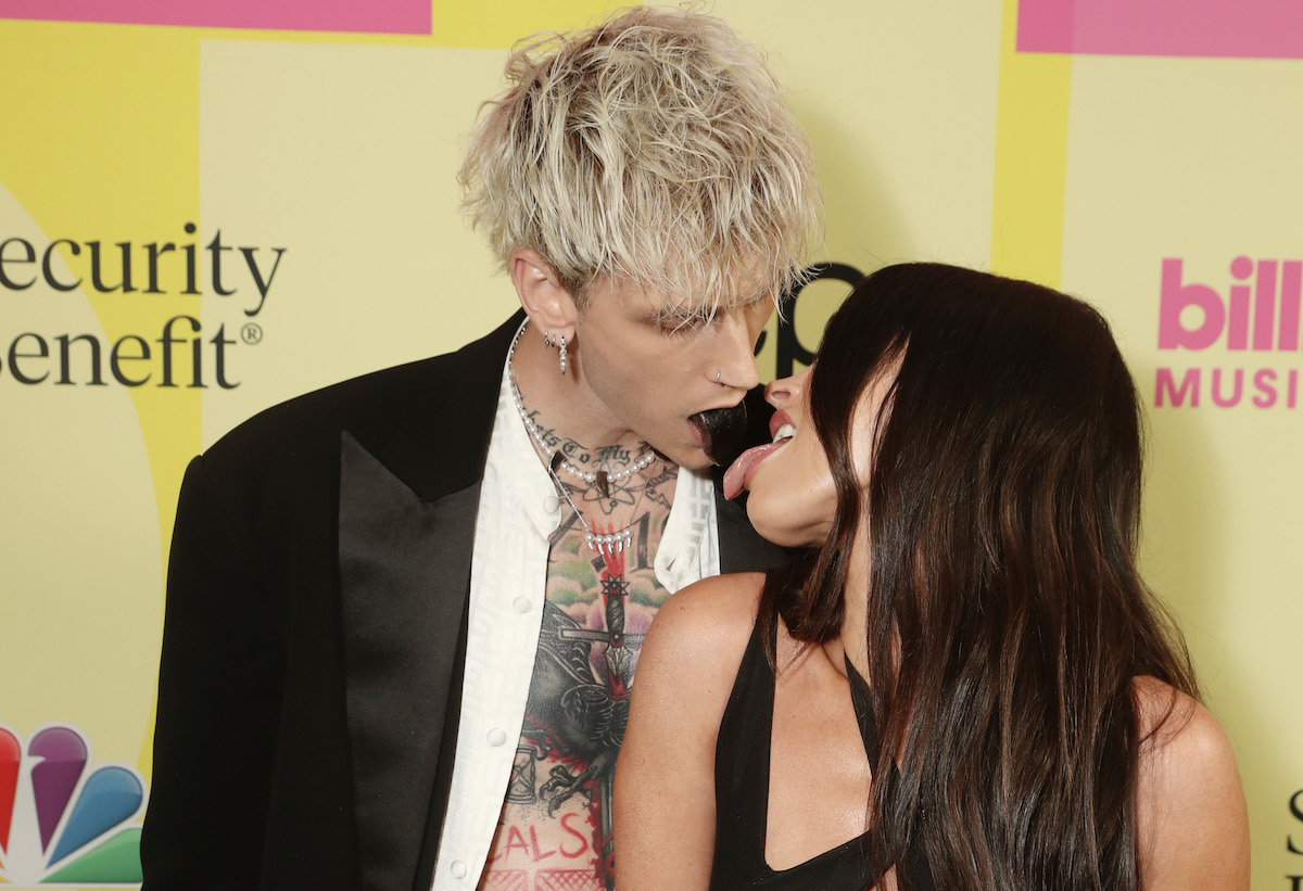 Machine Gun Kelly and Megan Fox touch tongues at an event.