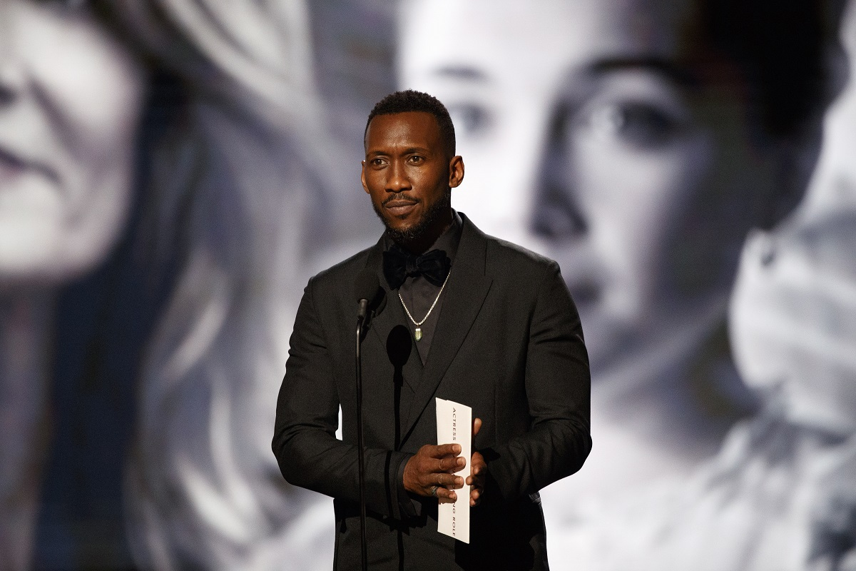 Mahershala Ali posing in front of a microphone