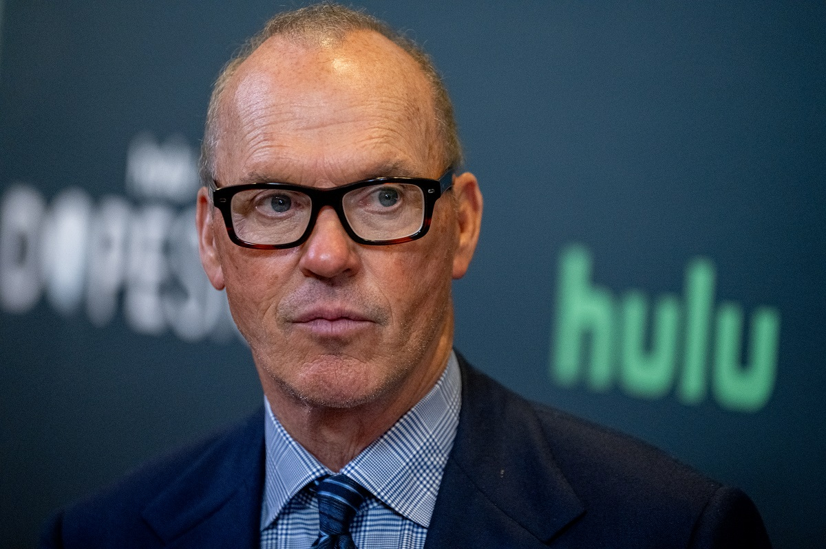 Michael Keaton staring while wearing glasses and a suit