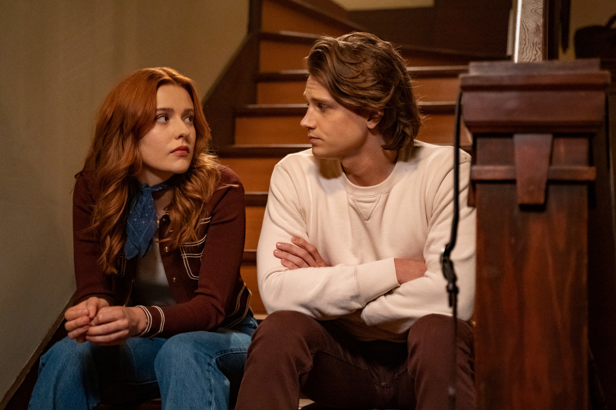 'Nancy Drew' stars Kennedy McMann and Alex Saxon, in character as Nancy and Ace, or 'Nace,' sit on a set of stairs. Nancy wears a brown jacket, jeans, and a blue scarf. Ace wears a white long-sleeved shirt and brown pants.