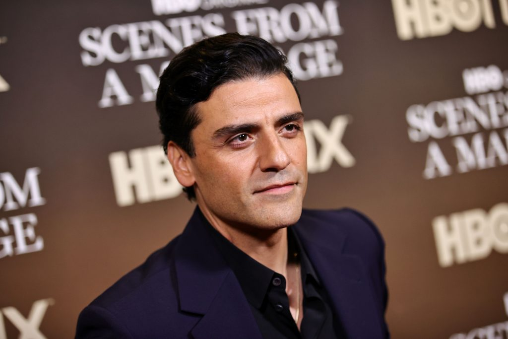 Oscar Isaac standing in front of a brown background with writing on it dressed in black.
