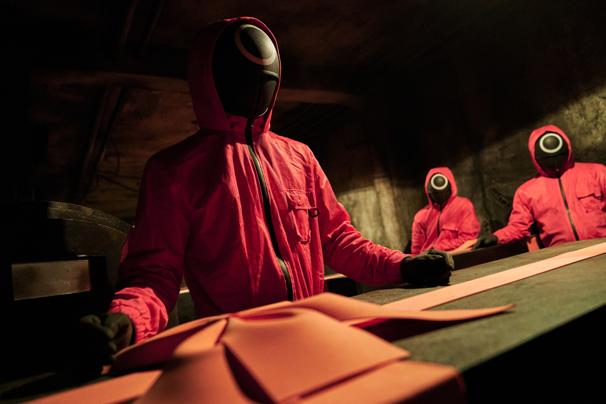 Workers in a pink and black jumpsuits move black coffins tied with pink bows in Squid Game.