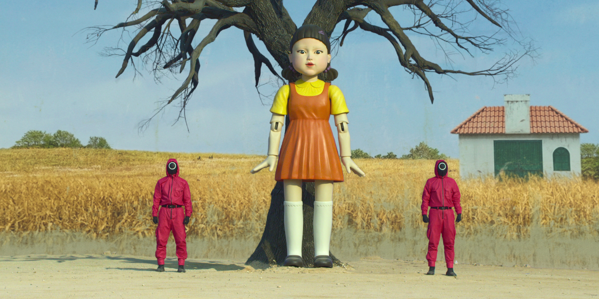 Two workers in pink jumpsuits stand beside the Squid Game doll in episode 1 of the Netflix series.