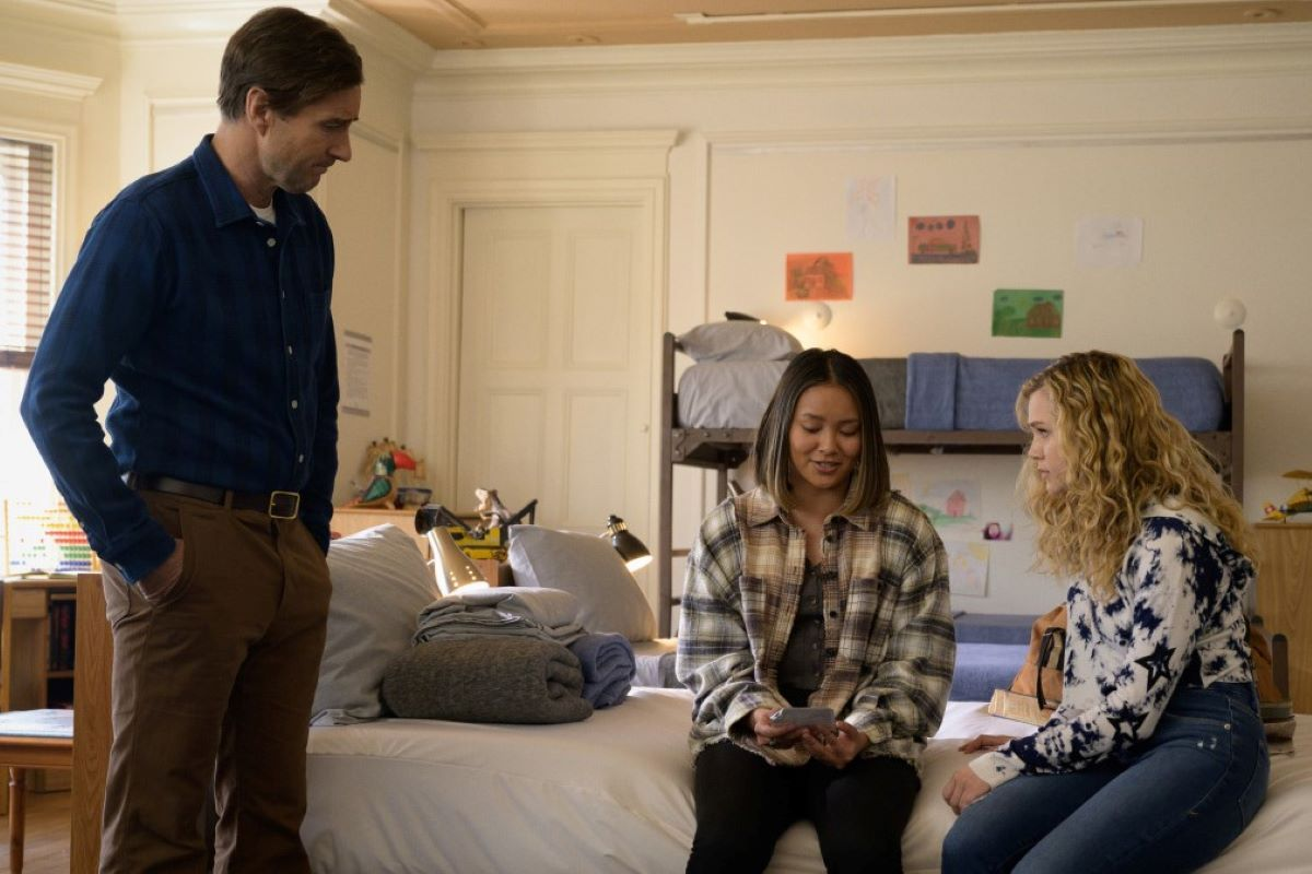 'Stargirl' actors Luke Wilson, Ysa Penarejo, and Brec Bassinger, all in character as Pat, Jennie, and Courtney, gather in a youth rehabilitation center. Jennie and Courtney sit on a bed while Pat stands above them. Pat wears brown pants and a blue button-up shirt. Jennie wears a white and green plaid shirt and black pants. Courtney wears a white and black tie dye hoodie and jeans.